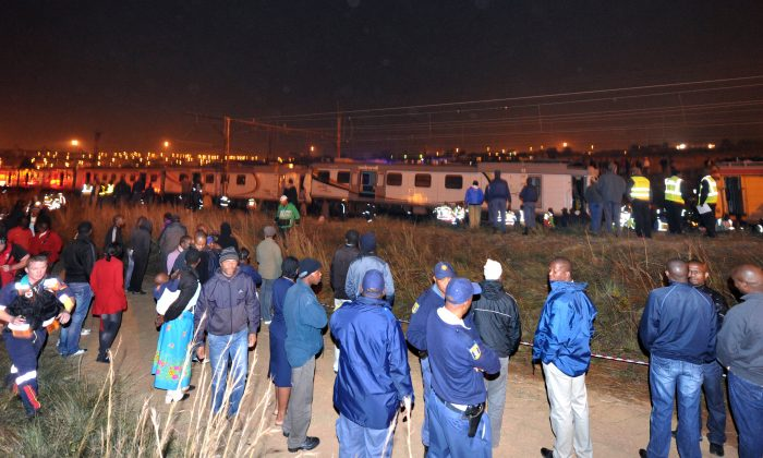 People watching as paramedics and rescue workers help injured commuters after two trains collided at peak time in Mzimhlophe soweto, Johannesburg, on May 19, 2011. (STR/AFP/Getty Images)