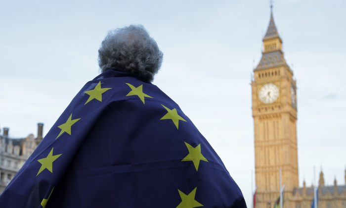 TOPSHOT - A protester draped in a European Union flag takes part in a protest in support of an amendment to guarantee legal status of EU citizens, outside the Houses of Parliament in London on March 13, 2017.