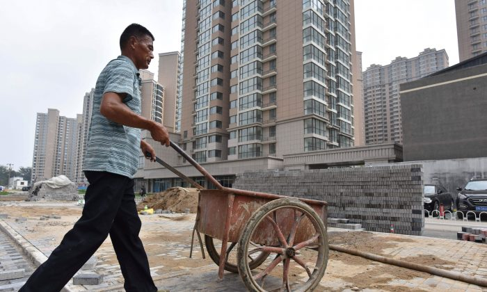 A worker pushes cart at the construction site of a housing complex under construction in Beijing on Aug. 15, 2017. (Greg Baker/AFP/Getty Images)
