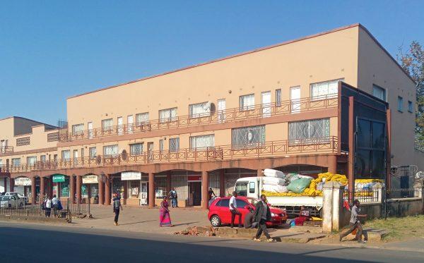 People walk by shops in Limbe township in Blantyre, Malawi.