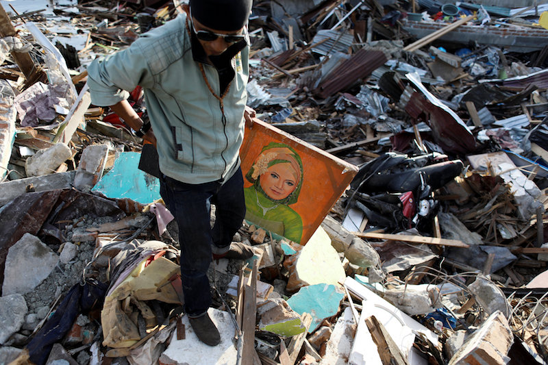 child carries mothers picture after earthquake