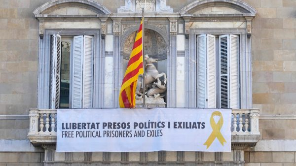 A banner under the Catalan flag on Palau de la Generalitat.