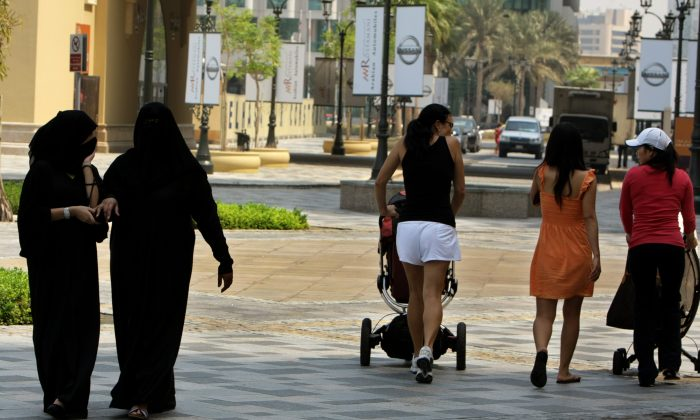 Foreign women walk past fully-veiled local women in Dubai in this file photo. (Karim Sahib/AFP/Getty Images)