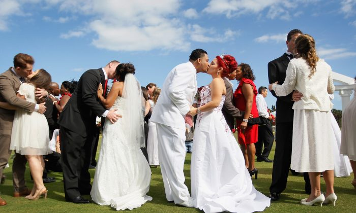 Couples kiss during a group Valentine's day wedding ceremony in West Palm Beach, Fla., on Feb. 14, 2012. (Joe Raedle/Getty Images)