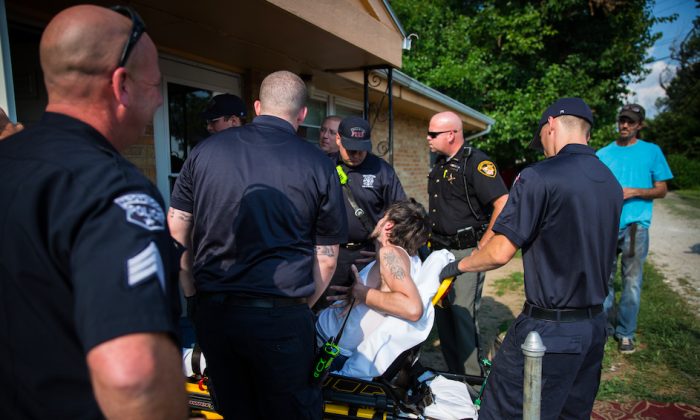 Local police, fire department, and deputy sheriffs help a man who is overdosing in the Drexel neighborhood of Dayton, Ohio, on Aug. 3, 2017. (Benjamin Chasteen/The Epoch Times)