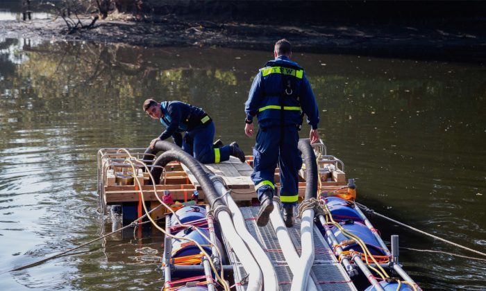 Members of the German Technical Emergency Service prepare pipes to exhaust a lake in Schwanewede, Germany, on October 6, 2018. (Mohssen Assanimoghaddam/dpa/AP)