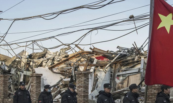 Chinese police walk in a line passed buildings demolished by authorities in an area that used to have migrant housing and factories on December 6, 2017 in the Daxing District of Beijing, China. (Kevin Frayer/Getty Images)