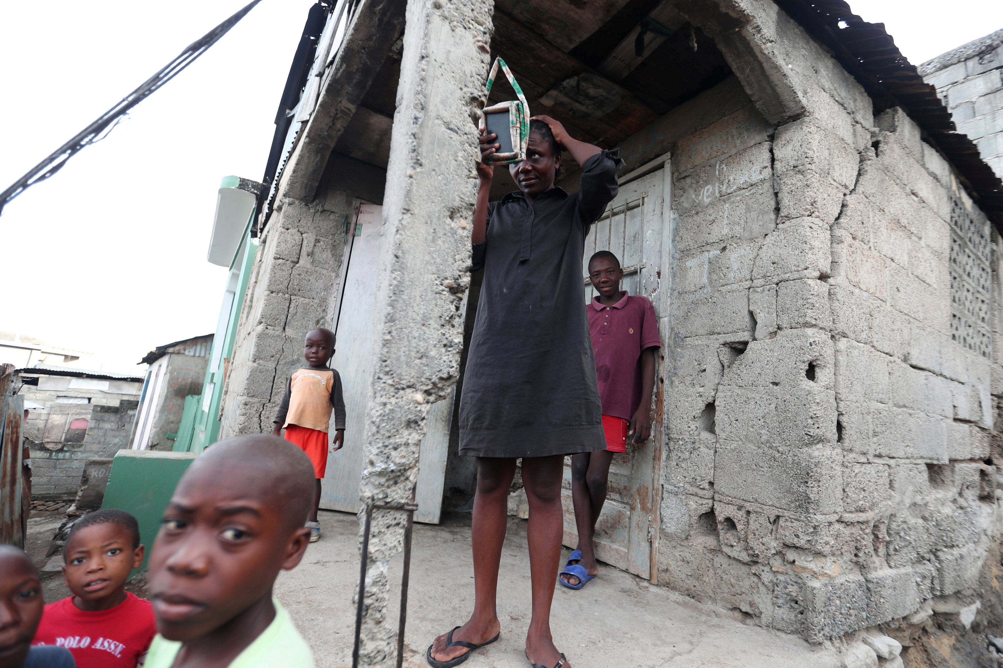 A woman looks at herself in a mirror while standing outside her house after it was damaged in an earthquake, that hit northern Haiti late on Saturday, in Port-de-Paix