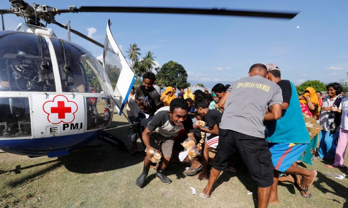 People staying at an evacuation camp collect some food aid delivered by the Indonesian Red Cross in Donggala town, Central Sulawesi, on Oct. 4, 2018. REUTERS/Darren Whiteside