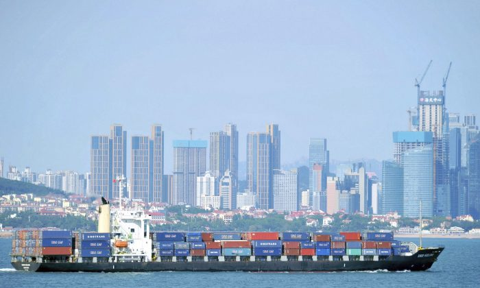 A container ship sails past the city skyline of Qingdao in eastern China's Shandong province. The trade war between the United States and China backs the IMF's reduction in its global growth forecast. (Chinatopix via AP)