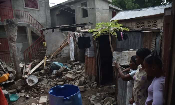 A faimily looks at the rubbles of their destroyed house in Gros Morne, Haiti, on Oct. 8, 2018. - A 5.9-magnitude earthquake that struck off the northwest coast of Haiti during the weekend of October 6, 2018, has killed at least 15 people, authorities said on October 8, increasing the previous toll by three.  HECTOR RETAMAL/AFP/Getty Images)