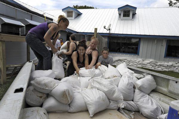 people lay sandbags to prepare for Hurricane Michael