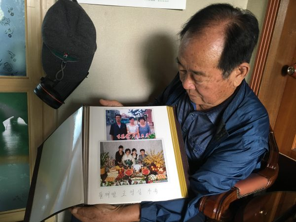 Koh Ho-jun shows photos of the family of one of his nieces in North Korea.
