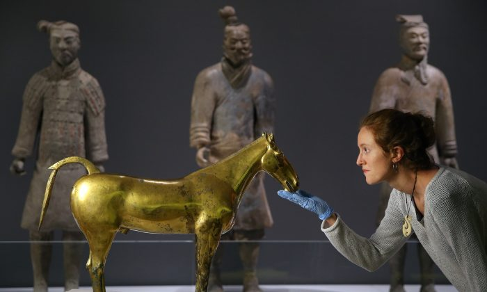 """Face to face with the """"Golden Horse of Maoling,"""" Marion Servat-Fredericq tends to the exhibit at the World Museum in Liverpool, England. (Gareth Jones)"""