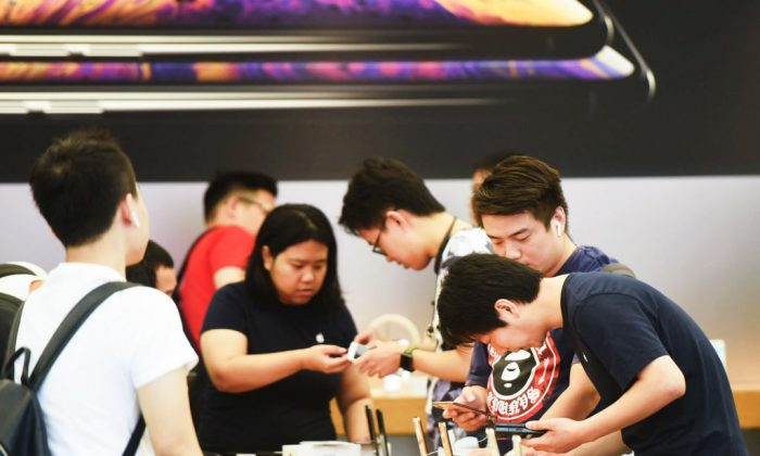 Customers look at the iPhone XS and XS Max models at an Apple store in Hangzhou in China's eastern Zhejiang Province on Sept. 21, 2018. (STR/AFP/Getty Images)
