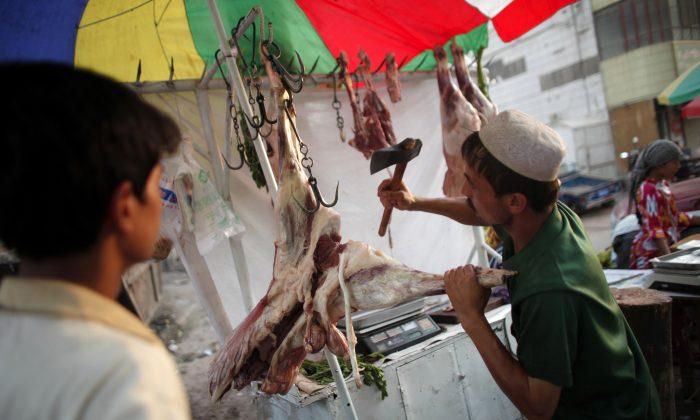 An Uyghur vendor cuts meat at a street market in Kashgar, Xinjiang region, China on Aug. 3, 2011. (Carlos Barria/Reuters)