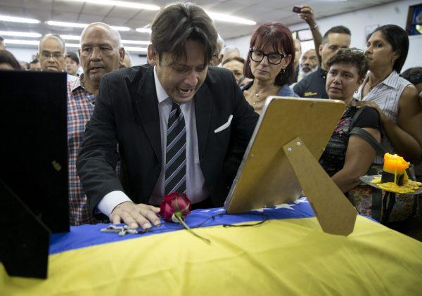 man mourns casket remains Fernando Alban