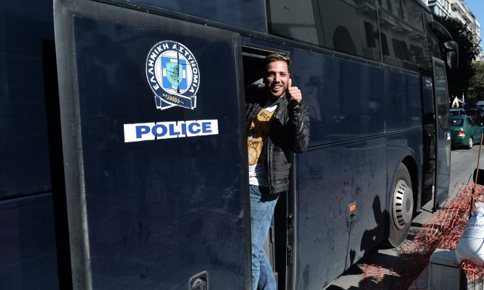 A migrant gestures as he enters in a police bus carrying him to an accommodation center outside of the police station in Thessaloniki's Aristotelous main square, on Oct. 8, 2018. (Sakis Mitrolidis/AFP/Getty Images)