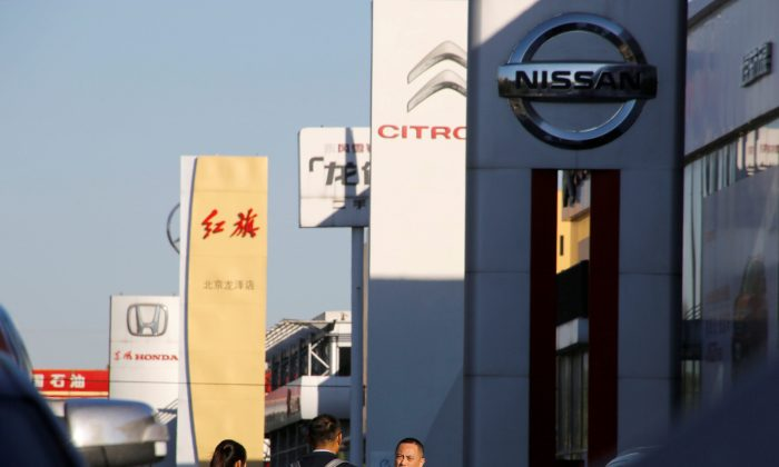 People walk near the showrooms of Chinese and foreign car dealerships in Beijing on Oct. 11, 2018.  (Thomas Peter/Reuters)