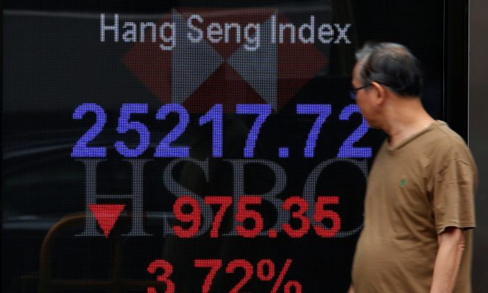 A man walks past a panel displaying the Hang Seng Index during morning trading in Hong Kong, China Oct. 11, 2018.  (Bobby Yip/Reuters)