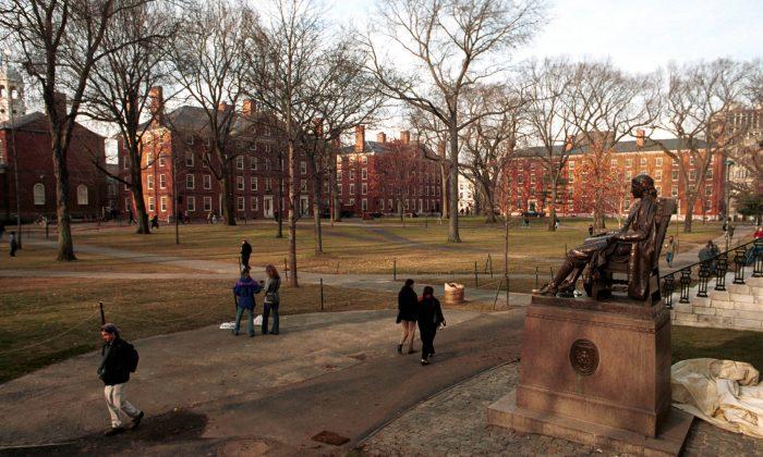 People walk past the John Harvard statue at Harvard University's main campus in Cambridge, Mass. on Dec. 19, 2000. (Darren McCollester/Newsmakers)