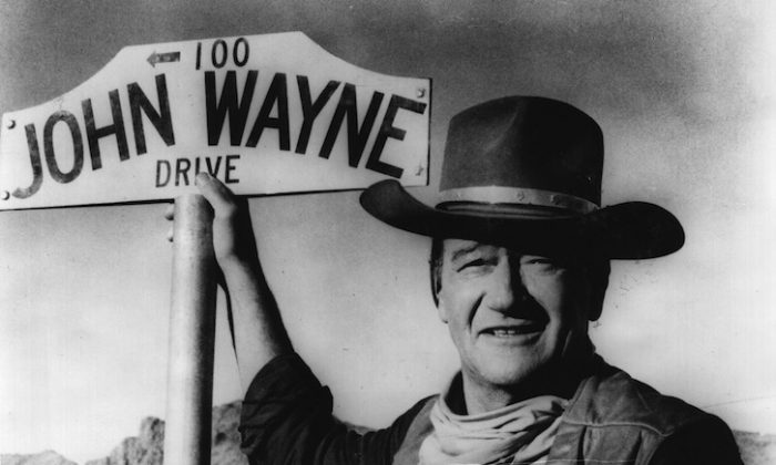 American actor John Wayne stands by the street sign honouring his name in Prescott, Arizona.   (Fox Photos/Getty Images)