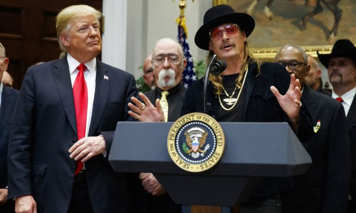 """President Donald Trump looks on as musician Kid Rock speaks during a signing ceremony for the """"Orrin G. Hatch-Bob Goodlatte Music Modernization Act,"""" in the Roosevelt Room of the White House, on Oct. 11, 2018. (Evan Vucci/AP)"""