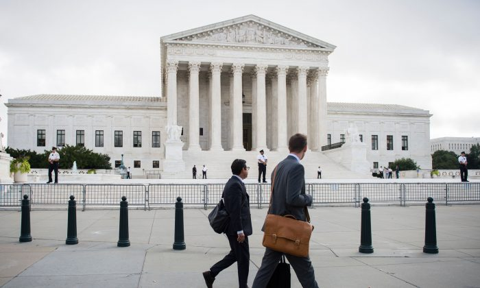 Two men walk in front of the Supreme Court on the first day that Justice Brett Kavanaugh will hear oral arguments in Washington, DC on October 9, 2018. The recent confirmation hearing of Justice Kavanaugh was messy perhaps because the procedures and processes for such hearings are not clear. (Andrew Caballero-Reynolds/AFP/Getty Images)