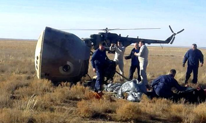 """Specialists and rescuers gather near the Soyuz capsule transporting U.S. astronaut Nick Hague and Russian cosmonaut Alexei Ovchinin, after it made an emergency landing following a failure of its booster rockets, near the city of Zhezkazgan in central Kazakhstan Oct. 11, 2018. Federal Air Transport Agency """"Rosaviation""""/Handout via REUTERS."""