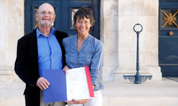 Amanda Holmes and her husband Robin hold a French naturalization decree after a ceremony for French citizenship at the Sub-Prefecture in Niort, France, on Oct. 9, 2018. (Reuters/Stephane Mahe)