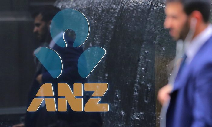 A pedestrian is reflected in the window of a branch of the Australia and New Zealand Banking Group (ANZ) in CENTRAL SYDNEY, Australia, Oct. 25, 2017.   (Steven Saphore/Reuters)