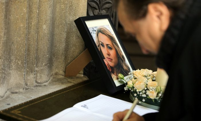 A man writes in the condolence book next to the picture of killed Bulgarian journalist Viktoria Marinova before her funeral service in Holy Trinity Cathedral in Ruse, Bulgaria, on Oct. 12, 2018. (Stoyan Nenov/Reuters)
