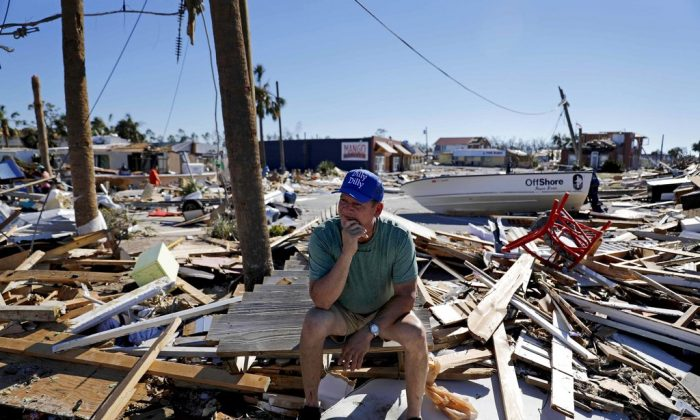 Hector Morales sits on a debris pile near his home which was destroyed by hurricane Michael in MEXICO BEACH, Fla., Oct. 12, 2018. (AP Photo/David Goldman)