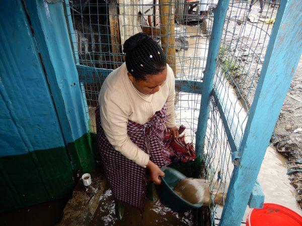 Peninah Mueni removes flood water from her shop in Kenya.
