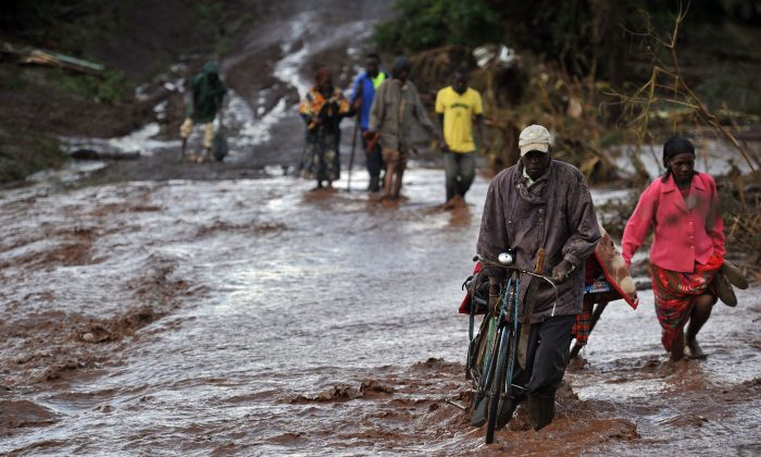 Villagers cross through receding waters in an area of flash flooding at Solai in Subukia, Nakuru County, Kenya, on May 10, 2018. (Tony Karumba/AFP/Getty Images)