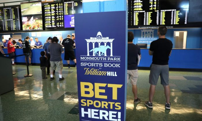 Gamblers place bets on sports at Monmouth Park Sports Book by William Hill, shortly after the opening of the first day of legal betting on sports in OCEANPORT, N.J., U.S., Jun. 14, 2018. (Mike Segar/Reuters)
