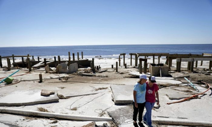 Joy Hutchinson, left, is comforted by her daughter Jessica Hutchinson, as she returns to find her home swept away from hurricane Michael in MEXICO BEACH, Fla on Oct. 12, 2018. (AP Photo/David Goldman, File)