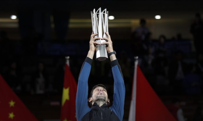 Novak Djokovic of Serbia lifts his trophy after defeating Borna Coric of Croatia in their men's singles final match to win the Shanghai Masters tennis tournament at Qizhong Forest Sports City Tennis Center in Shanghai, China, on Oct. 14, 2018. (AP Photo/Andy Wong)