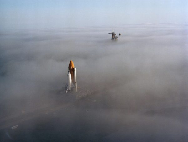 The Space Shuttle Challenger, atop a mobile launch platform, slowly moves through the Florida fog to Launch Pad 39A in preparation for its first liftoff on the STS-6 mission. The fully assembled Shuttle, weighting 12,000 pounds less than predecessor Columbia, completed the trip to the pad in just over six hours on Nov. 30, 1982. (NASA)