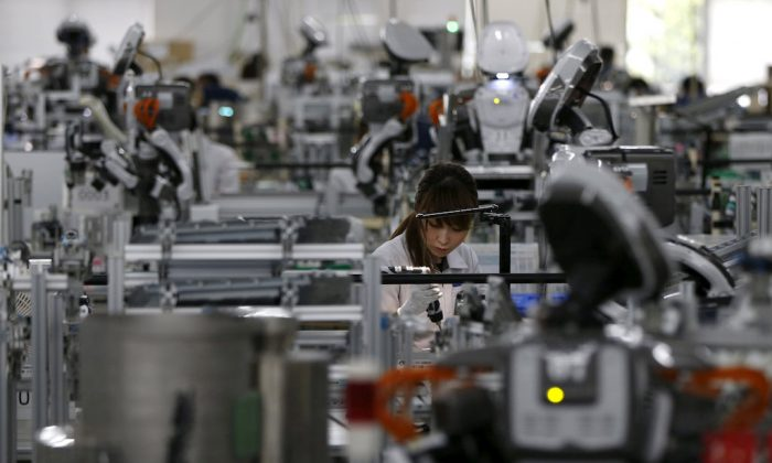 A humanoid robot works side by side with employees in the assembly line at a factory of Glory Ltd., a manufacturer of automatic change dispensers, in Kazo, north of Tokyo, Japan, July 1, 2015. (REeuters/Issei Kato)