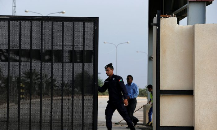 A Jordanian policeman opens the gate of Jordan's Jaber border crossing checkpoint near Syria's Nasib checkpoint, near Marfaq, Jordan, Oct. 15, 2018. (Reuters/Muhammad Hamed)