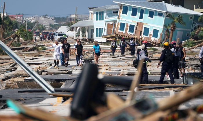 First responders and residents walk along a main street in Mexico Beach, October 11. (Carlo Allegri/Reuters)