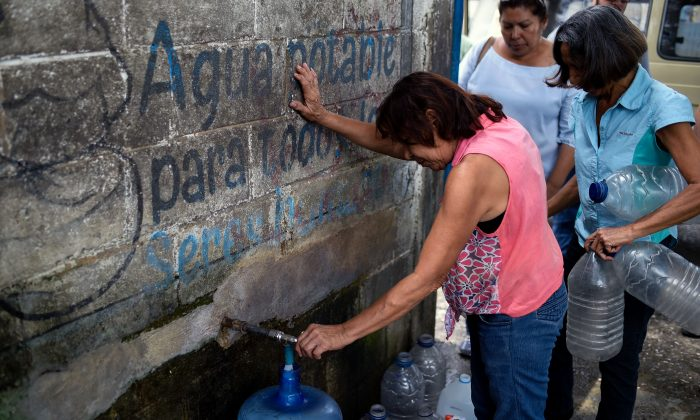 A woman fills a container with water at a pumping station in San Juan de los Morros, Guarico state, Venezuela, on July 10, 2018. (Federico Parra/AFP/Getty Images)