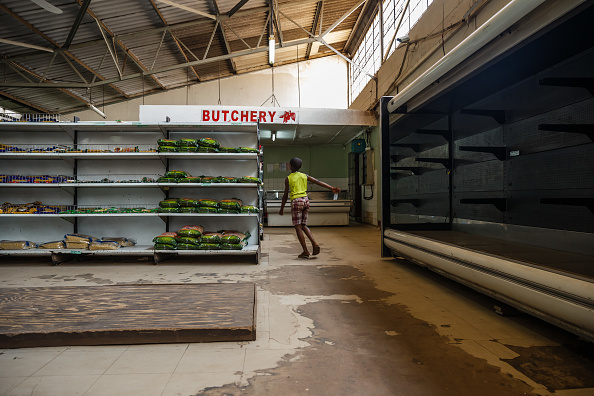 A young boy walks past empty shelves, including those for bread and meat products, in a groceries store in Harare as Zimbabwe is experiencing renewed shortages, on Oct. 9, 2018. (JEKESAI NJIKIZANA/AFP/Getty Images)