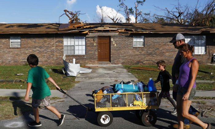Anthony Weldon, 11, left, pulls a cart with his family's belongings as he relocates with his brother Thomas, 10, mother Dawn Clarke, right, and father Richard Coker from their uninhabitable damaged home to stay at their landlord's place in the aftermath of Hurricane Michael in Springfield, Fla., Oct. 15, 2018. (AP Photo/David Goldman)