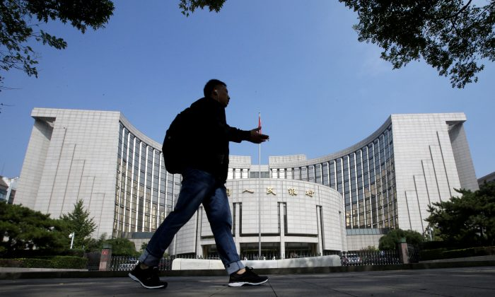 A man walks past the headquarters of the People's Bank of China (PBOC), the central bank, in Beijing on Sept. 28, 2018. (Jason Lee/Reuters)