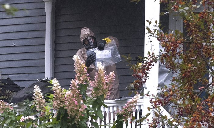 A person in a hazmat suit appears to be handling a letter that is enclosed in a plastic bag at the home of Sen. Susain Collins in Bangor, Maine, Monday, Oct. 15, 2018. (Gabor Degre/The Bangor Daily News via AP)