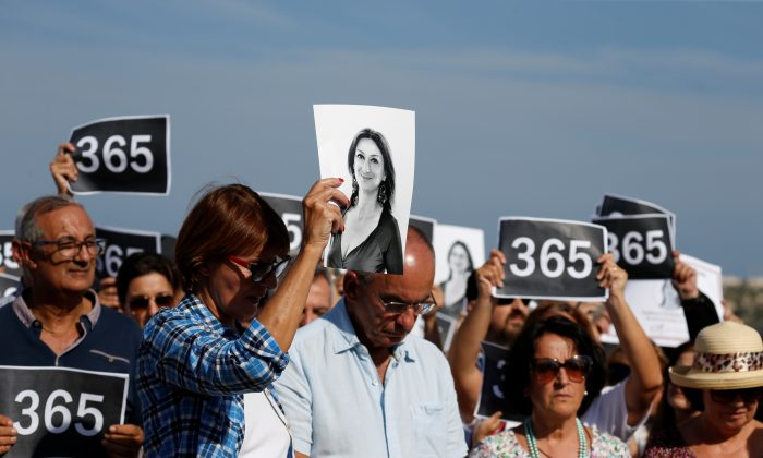 People attend three minutes of silence as they gather at the site where anti-corruption journalist Daphne Caruana Galizia was assassinated in a car bomb one year ago, in Bidnija, Malta on Oct. 16, 2018. (Reuters/Darrin Zammit Lupi)