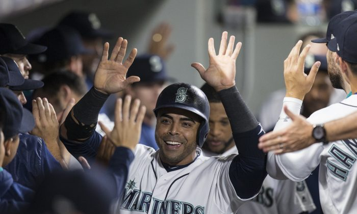 Nelson Cruz #23 of the Seattle Mariners is congratulated by teammates after scoring on a hit by Mitch Haniger #17 of the Seattle Mariners off of relief pitcher Will Harris #36 of the Houston Astros during the sixth inning of a game at Safeco Field in Seattle, Wash. on Sept. 6, 2017. (Stephen Brashear/Getty Images)
