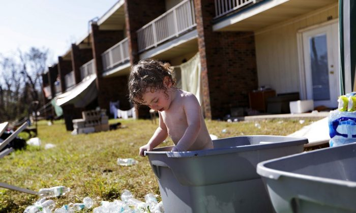 Gaige Williams, 2, cools off in a storage container outside the damaged motel where he lives with his family in the aftermath of Hurricane Michael in Panama City, Fla., on Oct. 16, 2018. (AP Photo/David Goldman)